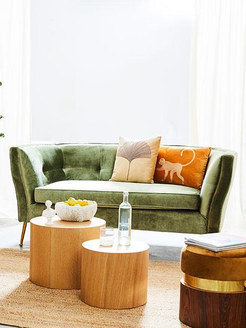 zielona sofa z pomarańczową poduszką przy drewnianych stolikach kawowych