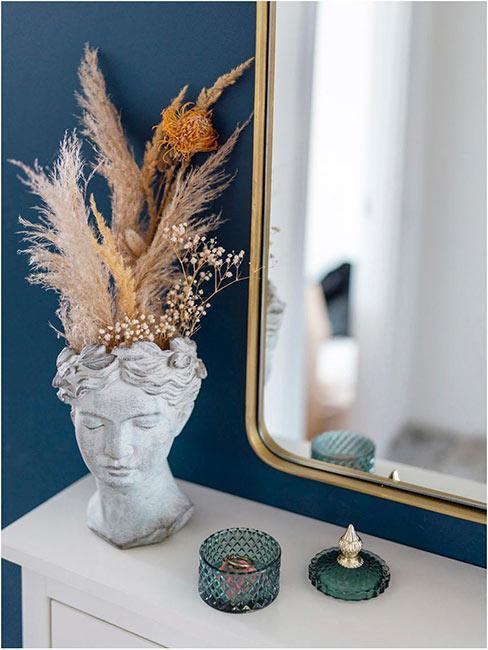 suszone kwiaty w wazonie w kształcie głowy na tle niebieskiej ściany