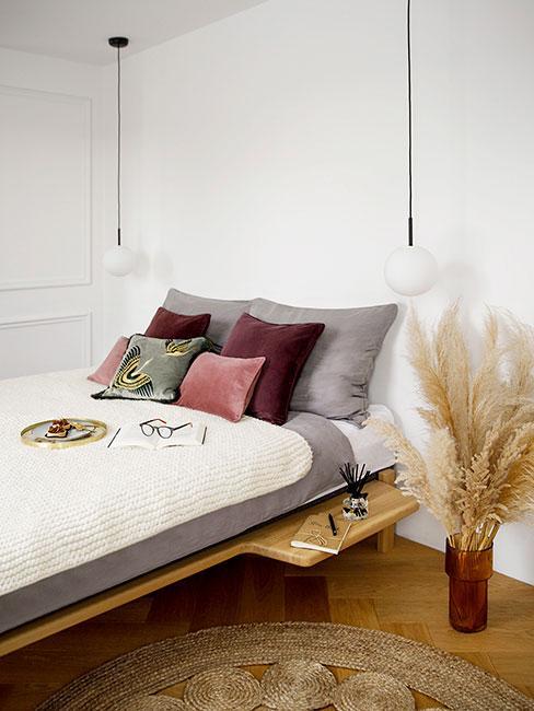 nowoczesny sypialnia z suszonymi trawami w wazonie i poduszkami w kolorach jesieni