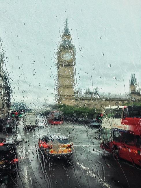 Krople deszczu na oknie z tłem miasta