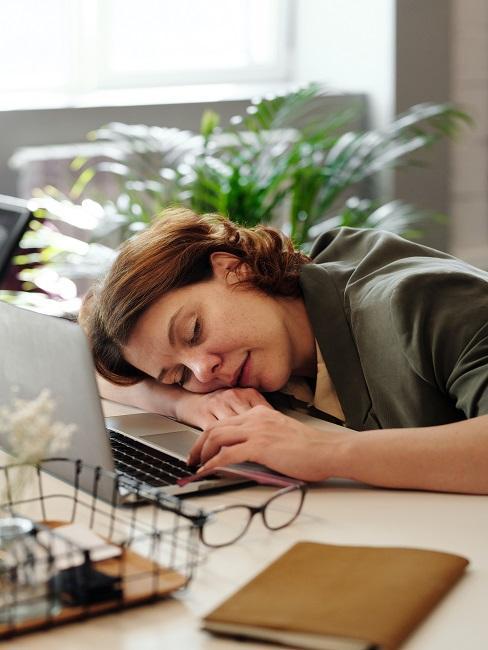 Kobieta śpiąca na biurku ze zmęczenia