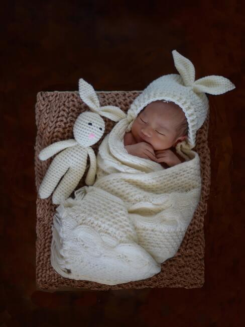 prezent na baby shower: dziecko ubrane w biały komplet z czapką z uszami i zajączkiem obok