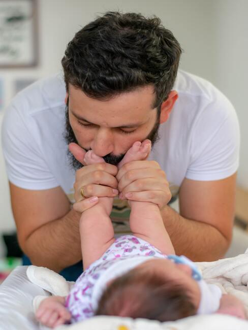 Tata całujący nogi małego dziecka