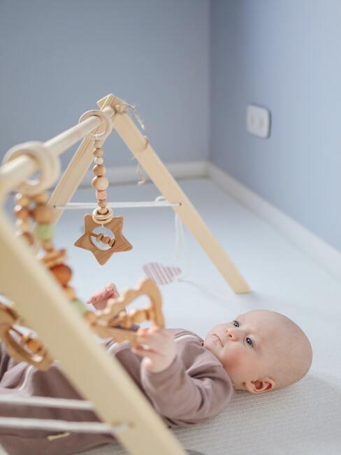 prezent na baby shower: Zabawka dla dziecka z różnymi wiszącymi elementami a pod nią zapatrzone dziecko