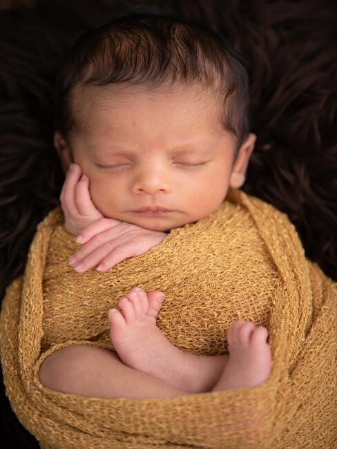 spiące dziecko otulone w żółty koc przytrzymujące sobie dłonią buzie