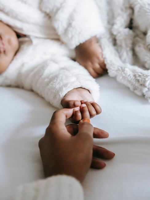 Mała rączka dziecka trzymająca dłoń dorosłego człowieka