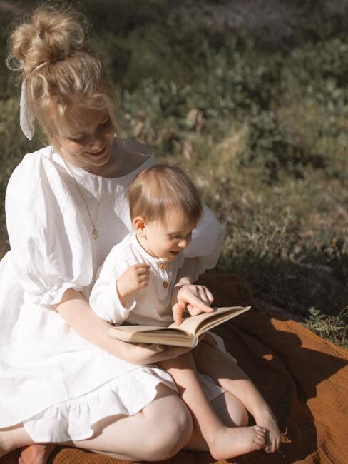 gratulacje z okazji narodzin dziecka: Kobieta ubrana w białą sukienkę, trzymająca dziecko na rękach wraz z książką którą razem przeglądają