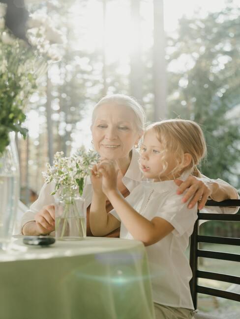 gratulacje z okazji narodzin dziecka: babcia z wnuczką w ogrodzie bawiące się bukietem polnych kwiatów