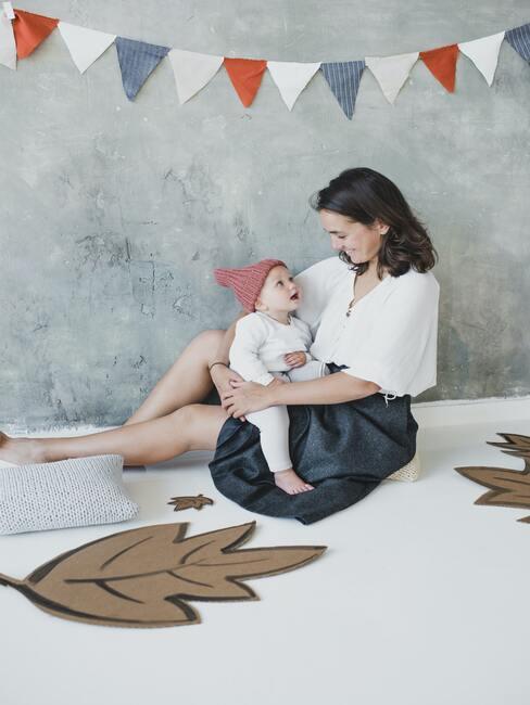 gratulacje z okazji narodzin dziecka: mama trzymająca dziecko na kolanach