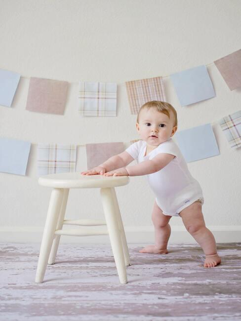 male dziecko podtrzymujące się stołka na tle beżowej ściany z zawieszonymi aplikacjami