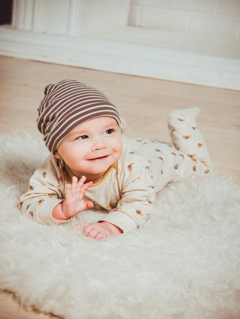 dziecko w beżowym body ze wzorami, z czapką na głowie leżące na dywanie
