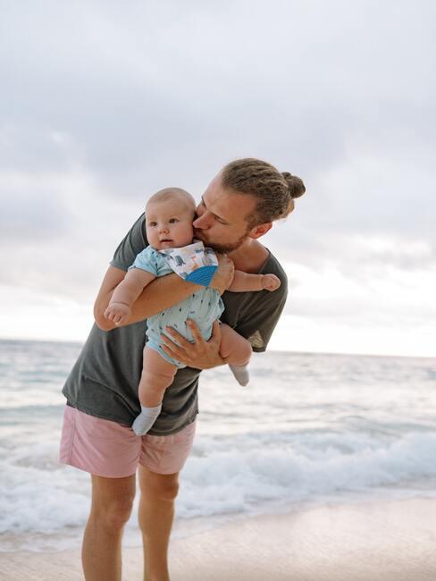gratulacje z okazji narodzin dziecka: tata trzymający dziecko na rękach w marskiej scenerii