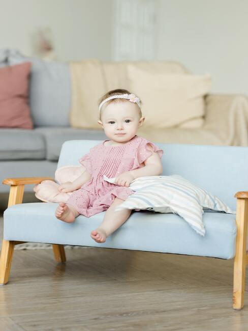 mała dziewczynka na sofie ubrana w różowe ubranko z opaską na głowie