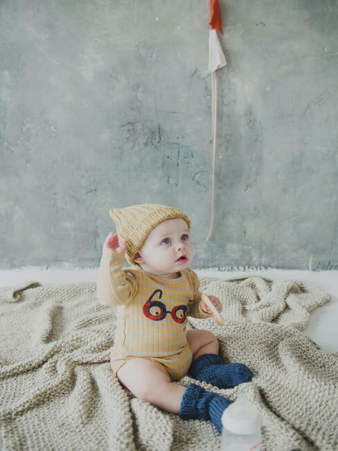 mały chłopiec ubrany w beżowy kubraczek