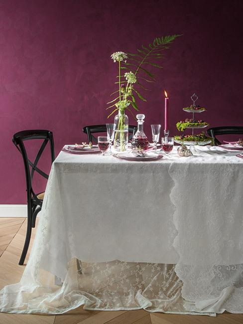 burgundowa ściana w jadalni przy stole z białym obrusem i czarnymi krzesłami