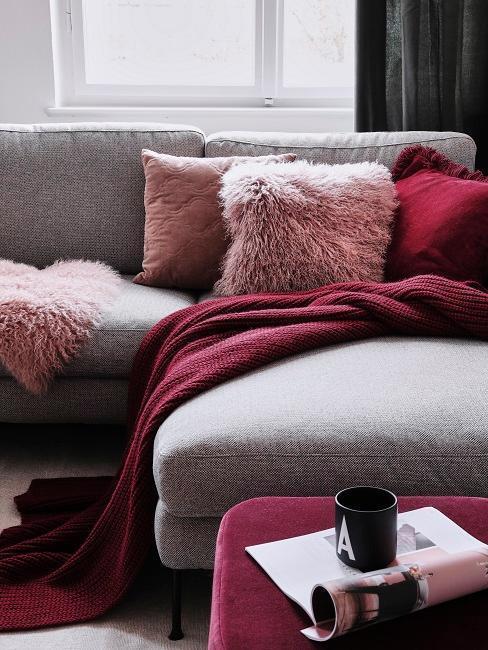 tekstylia w kolorze burgundowym i pudrowym różu na szarej sofie