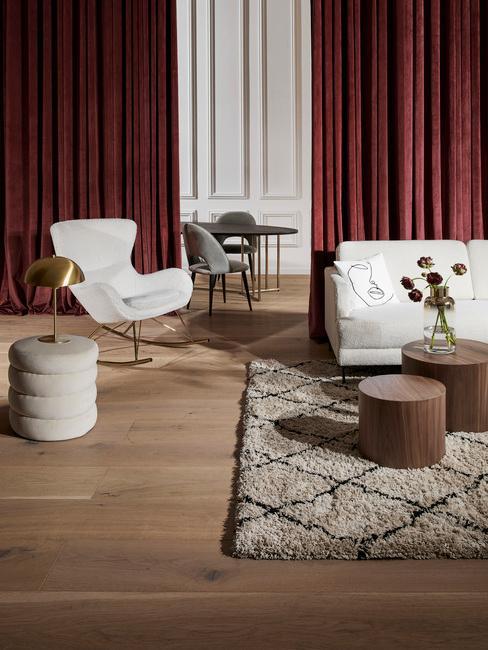 burgundowe zasłony w salonie z białym fotelem bujonym boucle i białą sofą