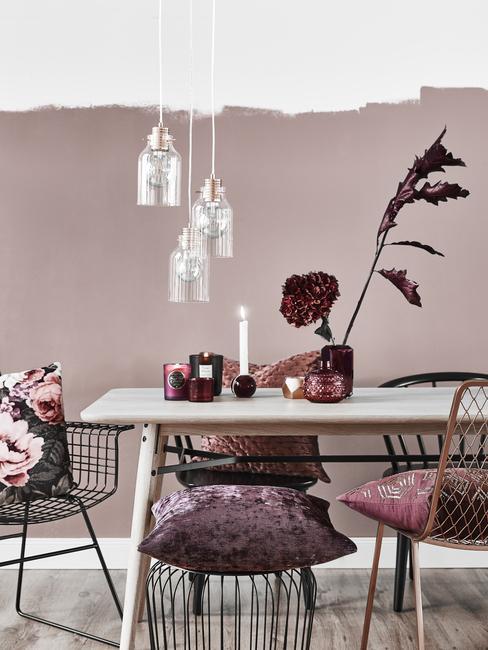 Dodatki w kolorze burgundu w jadalni z białym stołem na tle fioletowej ściany