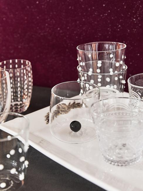 burgundowa ściana na tle szklanek na białej tacy