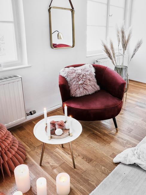 fotelburgundowy fotel z aksamitu obok białego stlika pomocniczego i różową poduszka z futra