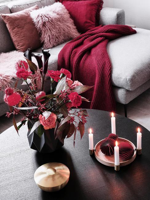kwiaty w kolorze burgundowym na ciemnym drewnianym stoliki kawowym przed szarą sofą