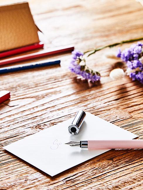 biała kartka na drewnianym biurku obok otwartego pióra wiecznego