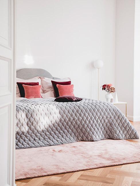 jasna sypialnia w stylu glamour z szarą narzutą i puduszkami w kolorze burgundu i łososiowym