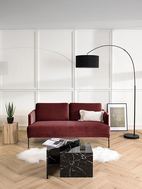 mała burgundowa sofa z aksamitu w nowoczesnym salonie przy czarnej lampie podłogowej