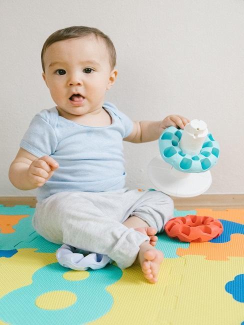 Dziecko trzymające zabawkę na macie
