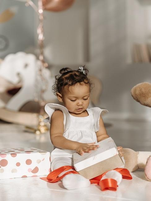 Dziewczynka rozpakowująca prezent na chrzest