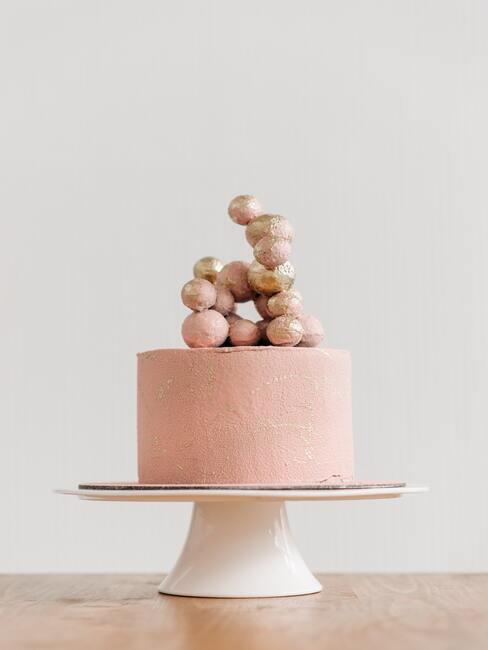 Minimalistyczny różowy tort z ozdobnymi kulkami w kolorze złota