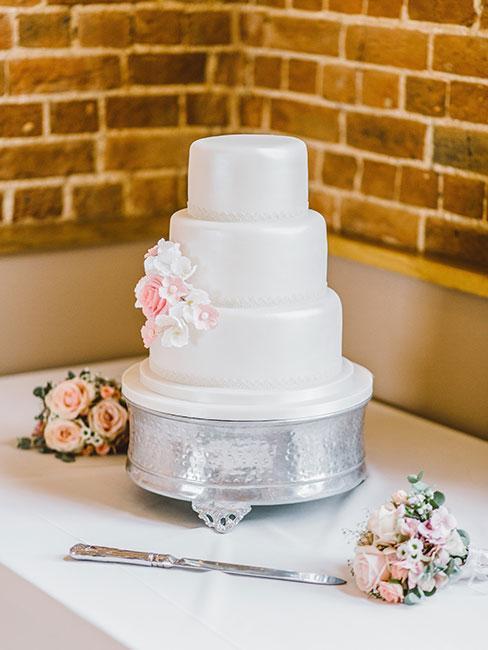 Biały tort z w trakcie ozdabiania bladoróżowymi kwiatkami