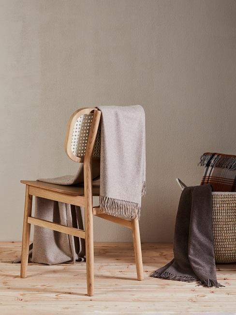 Krzesło z kocem na tle ściany w kolorze taupe