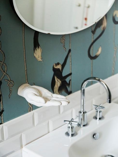 Ściana łazienki w kolorze morskim z białymi dodatkami i wzorem w małpki