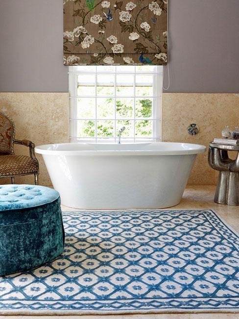 Luksusowa łazienka z wolnostojącą wanną i roletą z motywem ptaków obok tapicerowanego fotela i pufy z funkcją przechowywania