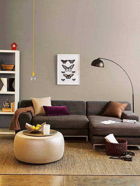 sofa w kolorze antracytowym na tle ściany w kolorze taupe z poduszkami w kolorze burgundu i karmelu