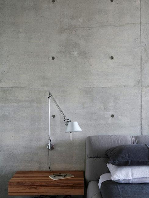 Minimalistyczne wnętrze z betonową ścianą, drewnianą podłogą oraz kanapa w szarym kolorze i lampą podłogową