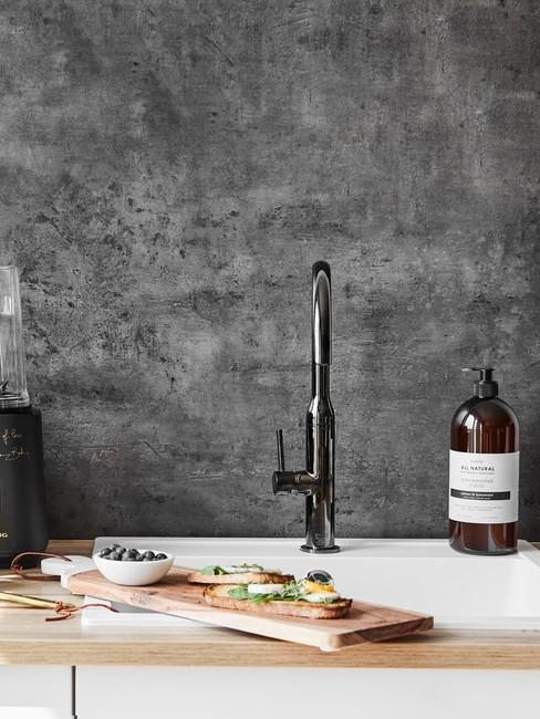 Zlew kuchenny w białym kolorze z baterią w ciemnym odcieniu metalu na tle ciemnej betonowej ściany