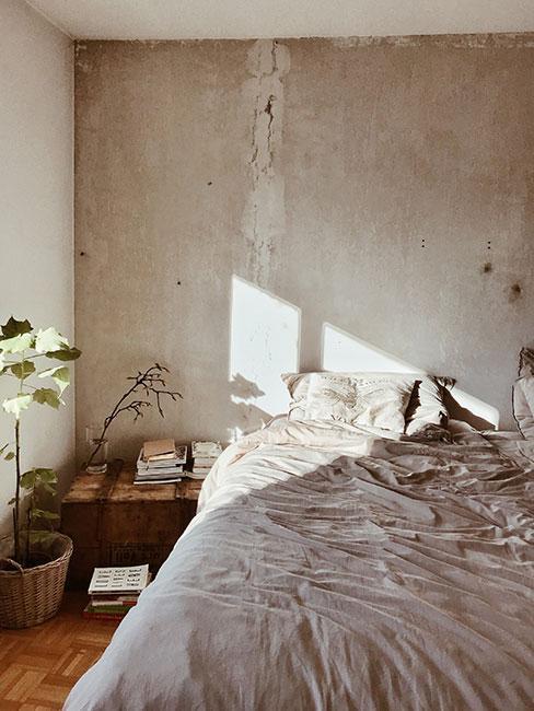 betonowa ściana w sypialni, drewniana szafka nocna, rośliny i proste łóżko z pościelą w neutralnym kolorze