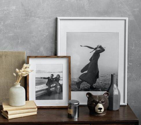 Dodatki w postaci zdjęć i figurek na komodzie z ciemnego drewna na tle betonowej ściany