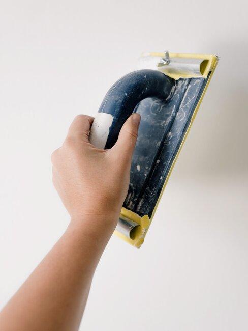Ręka nanosząca tynk na ścianę
