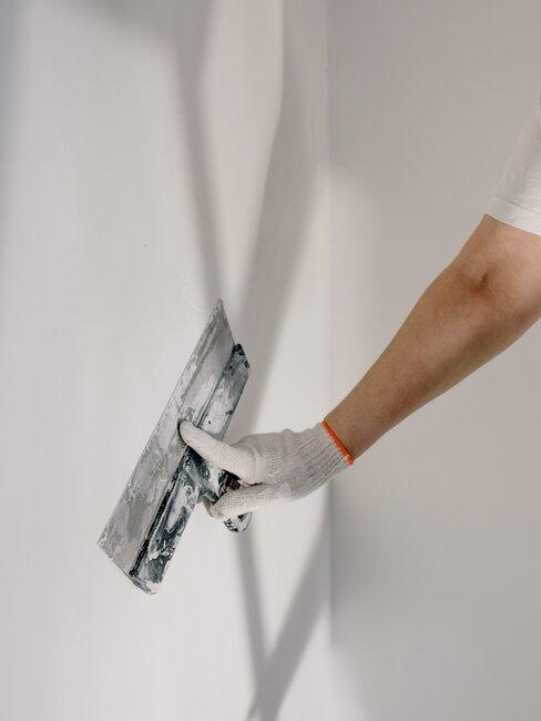 Osoba pokrywająca ścianę tynkiem