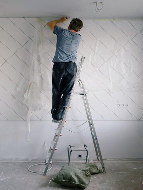 Osoba na drabinie przygotowująca ścianę do malowania