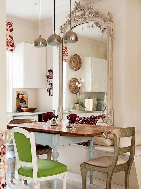 Beżowa kuchnia z wielkim lustrem na ścianie w ozdobnej ramie, stołem z drewnianym blatem i krzesłami w różnych kolorach