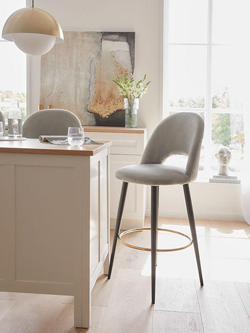 Kuchnia w odcieniach beżu z jasnymi dodatkami i szarym krzesłem