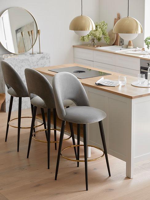 Beżowa kuchnia, wyspa na środku a obok szare krzesła