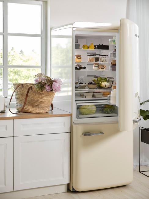 Beżowa lodówka w kuchni z białymi szafkami i koszem świeżych kwiatów na blacie