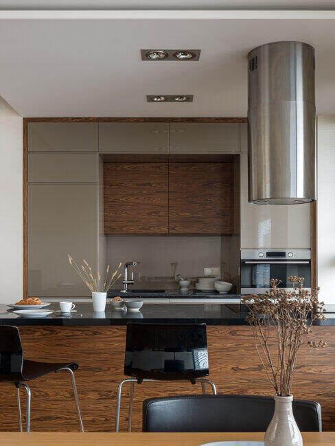Beżowe szafki w kuchni, drewniana wyspa i czarne krzesło