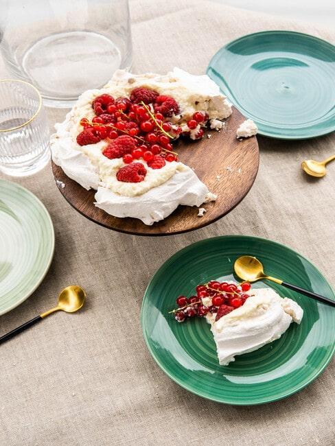 Wegański tort Pavlova na stole nakrytym pastelowym talerzami
