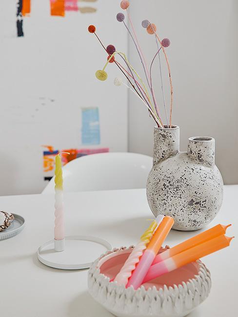 dwukolorowe świeczki na białym stole na tle jasnego pokoju